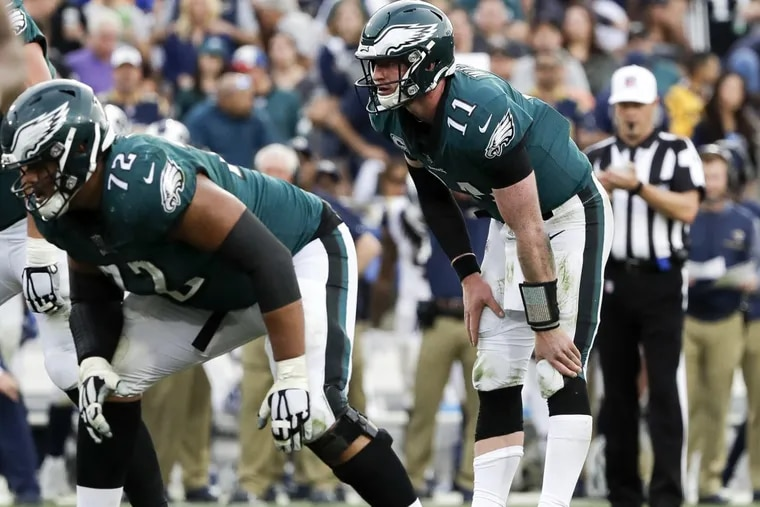 Eagles quarterback Carson Wentz rubs his knee before the Eagles scored in the third-quarter against the Los Angeles Rams on Sunday, December 10, 2017. YONG KIM / Staff Photographer