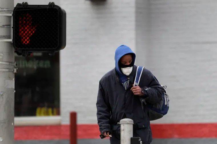 A man wears a protective mask as he waits to cross a street Monday, April 13, 2020, in St. Louis, where, as in Philadelphia, black residents are dying at a higher rate than other populations.