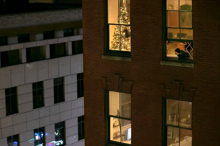 The holidays pose special challenges for isolation. Anna Evenosky, 22, looks out of her apartment window on Walnut Street in November when the physical therapy grad student was home to quarantine after she was exposed to COVID-19 by a lab partner, She put up the tree to keep her spirits up.