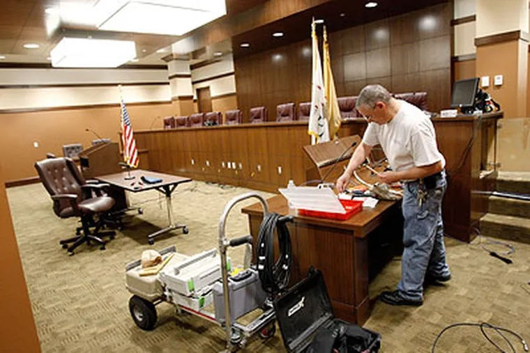 Chris Hughes finishes the audio/video wiring in the courtroom of the new Voorhees Township offices at the Voorhess Town Center, once the largest mall in South Jersey, on Friday. (Elizabeth Robertson / Staff Photographer)