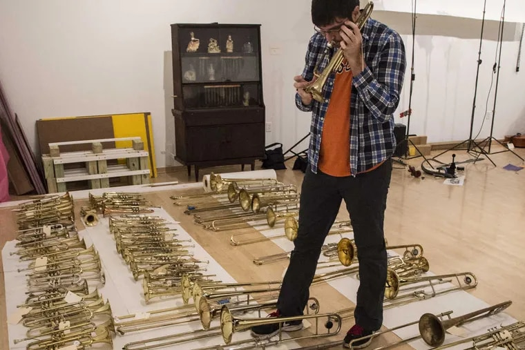 Connor Przybyszewski, 28, a Drexel grad and a professional musician living in West Philly, tries out a trombone in tTemple Contemporary, at Tyler School of Art as part of the Symphony for a Broken Orchestra exhibit.