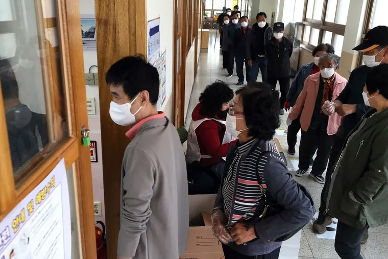 People wearing face masks to help protect against the spread of the new coronavirus wait in line to cast for their votes for the parliamentary elections at a polling station in Nonsan, South Korea, Wednesday, April 15, 2020.