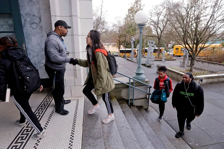 Teaching assistant Leonardo Baker, left, greets students arriving at Franklin High School in Seattle last year after the district changed from a 7:50 a.m. start time to 8:45 a.m. in an effort to fight teen sleep deprivation.