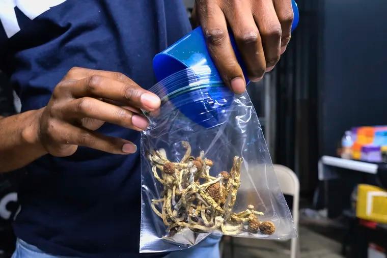 A vendor bags psilocybin mushrooms at a cannabis marketplace in Los Angeles.