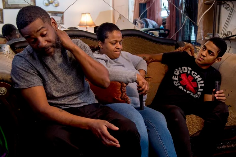 Troy and Debra Harris with their son Azir (right) at home. He was shot and paralyzed a year ago, and they have been looking for wheelchair-accessible public housing, but the waiting list is long.
