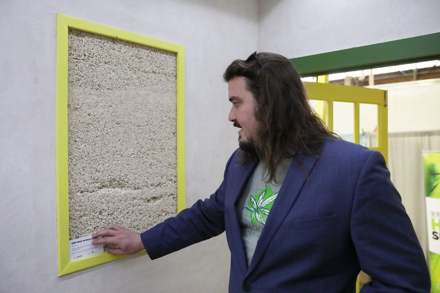 """Cameron McIntosh, builder of the """"Hemp House on Wheels,"""" talks about """"hempcrete"""" — a bio-composite insulation material — used in the house at the Pennsylvania Hemp Industry Council's exhibit during the annual Pennsylvania Farm Show at the Pennsylvania Farm Show Complex & Expo Center in Harrisburg, Pa., on Jan. 7, 2020."""