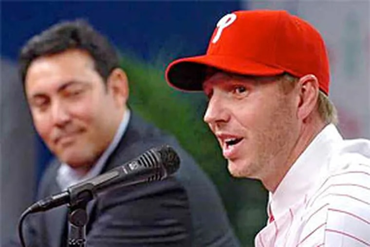 Roy Halladay, with Phillies general manager Ruben Amaro Jr., dons his Phillies hat and answers questions about his arrival. The ace pitcher welcomed the trade to Philadelphia. (Clem Murray / Staff Photographer)