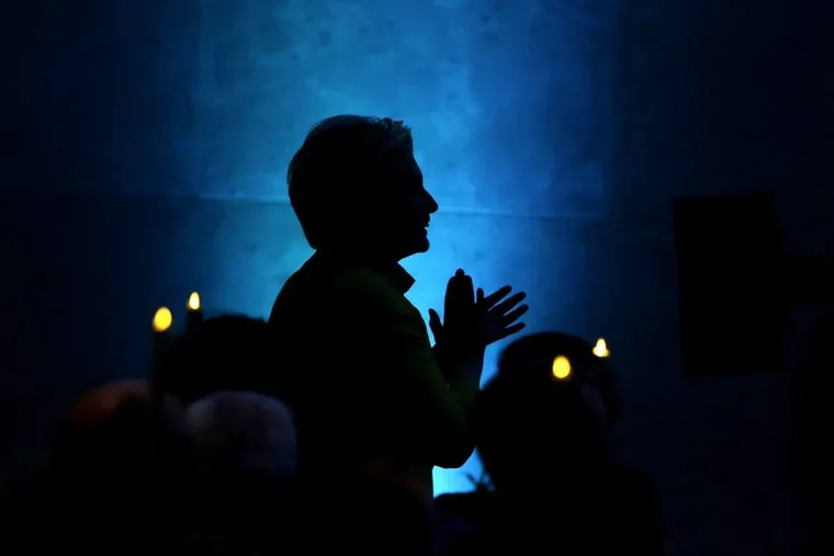 Former Secretary of State Hillary Clinton appears in silhouette as she applauds before taking the stage to speak during a fundraising event for Big Sister Association of Greater Boston, Tuesday, Dec. 5, 2017, in Boston.