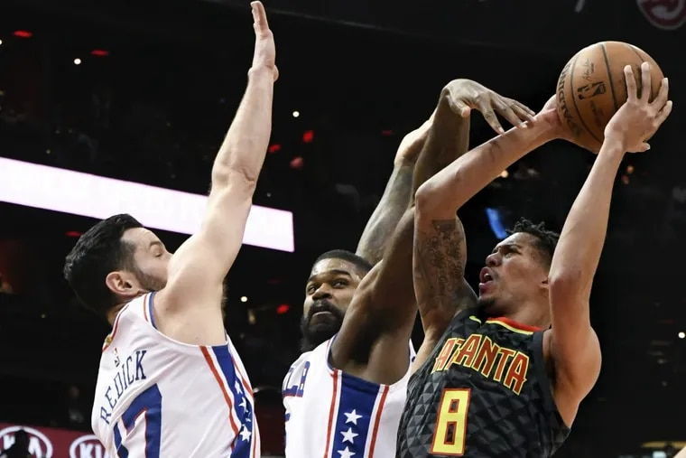 Sixers JJ Redick (17) and Amir Johnson defend Hawks guard Damion Lee (8), the former Drexel player, during the first half.