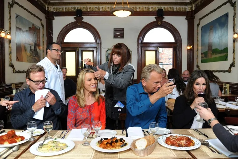 'Wheel of Fortune' host Pat Sajak offers a toast to tablemates as co-host Vanna White gets her hair adjusted inside Ralph's Italian Restaurant in Philadelphia. Sajak missed several episodes of the popular gameshow after a health care forced him into emergency surgery last month.