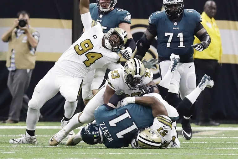 Carson Wentz gets sacked late in the second quarter by the Saints' Alex Okafor (on ground), defensive tackle David Onyemata and defensive end Cameron Jordan