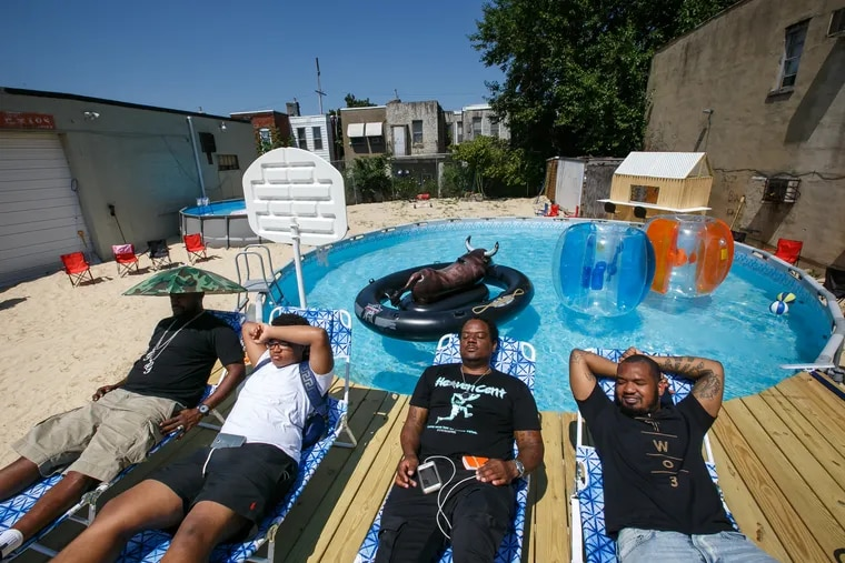 (Left to Right) Disco Inferno (nickname), Tariq Knight, his father and the owner of the lot, Chris Knight, and the promotor of the space, David Brown, relax poolside, this former parking lot in North Philly has been converted into a mini beach with sand, above ground pools, a wooden deck and beach furniture, in Philadelphia, Wednesday, July 11, 2018. This site will be the setting of an upcoming pool party.