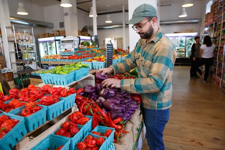 Riverwards produce owner Vincent Finazzo stacks produce in his store.