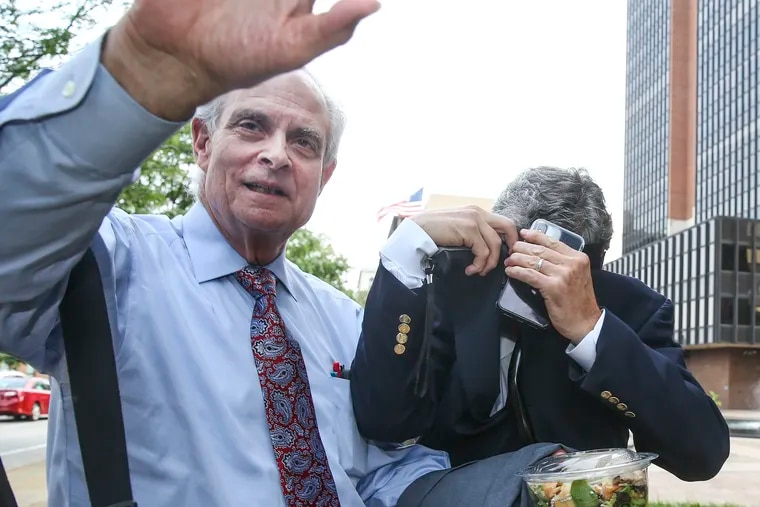 Peter Bistrian hides his face as he leaves the federal courthouse in Philadelphia with his lawyer Richard L. Bazelon (left) on Tuesday. Bistrian is suing the prison guards who he says failed to protect him while using him as an informant against violent drug lord Kaboni Savage.