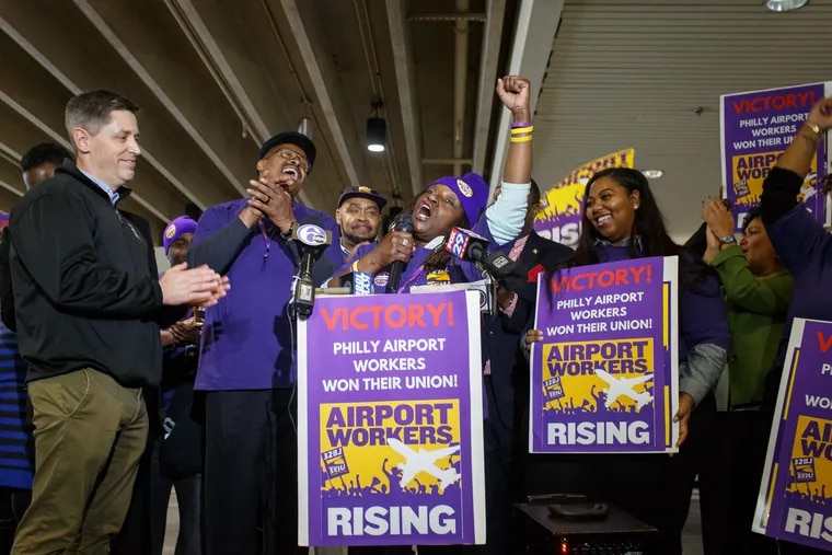 Airport wheelchair attendant Onetha McKnight (with microphone) celebrates with her coworkers in April 2017 after they voted to join union SEIU 32BJ.