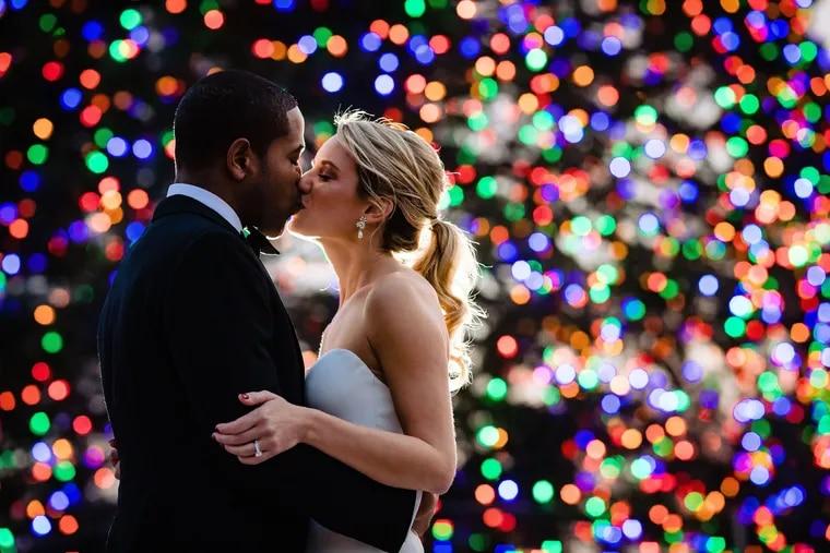 Robert (BJ) L. Glenn III (Groom) and Christina Zipf (Bride) kiss in front of Christmas tree at top of Philadelphia Museum of Art steps. Post-wedding/Pre-reception shoot in Philadelphia, PA.