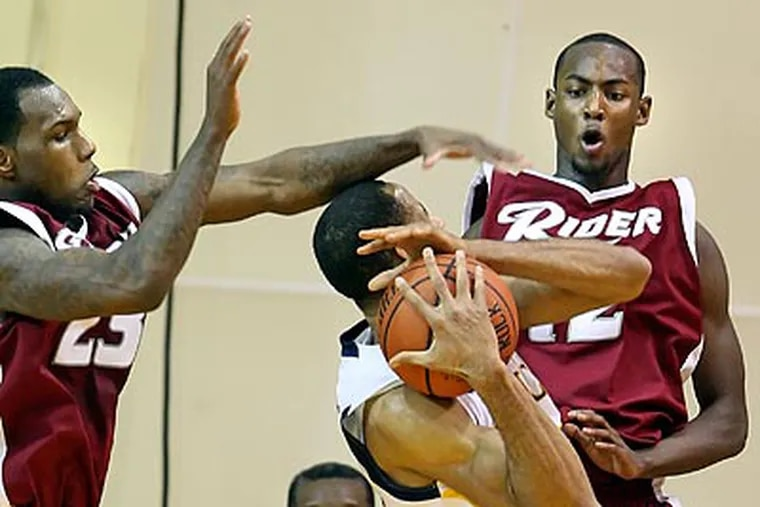 La Salle's Jerrell Williams gets fouled by Rider's Novar Gadson, left, during the second half. (Steven M. Falk / Staff Photographer)
