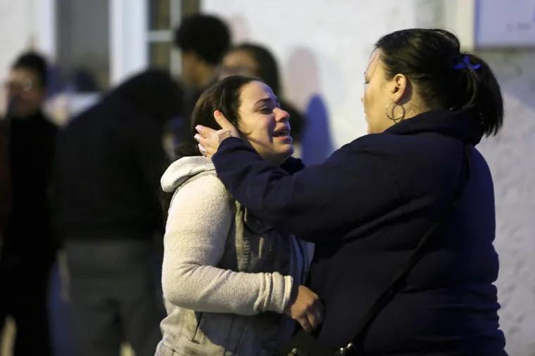 Residents grieve as on Jasper Street near Glenwood Avenue, Monday Nov. 23, 2015, in Harrowgate, where two men were found dead.