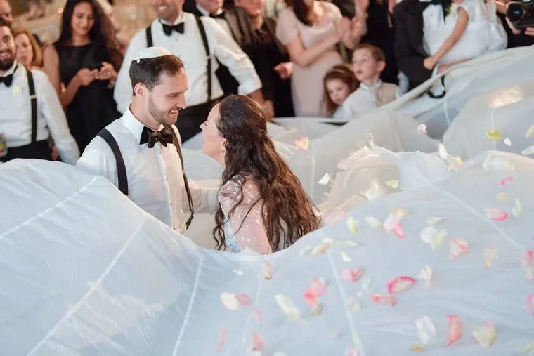 Arielle Belfer and Jacob Wischnia dance in the middle of a white parachute with flower petals, family and friends surrounding them.