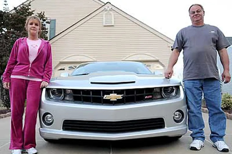 Gina and John Goral pose with the World Series MVP car initially delivered to Cole Hamels. (Kriston J. Bethel / Staff Photographer)