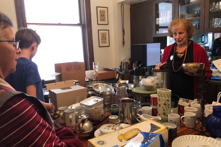 Karen Mulhauser (right) makes one of her announcements by pinging her Tibetan singing bowl. She's giving away her belongings to prepare to move to condo after 45 years in her D.C. home.