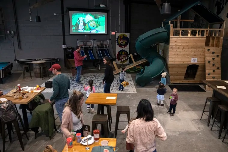 Families eat and hang out in the social space, which includes an indoor playground, video games and recreational games at Craft Hall in the Northern Liberties section of Philadelphia.
