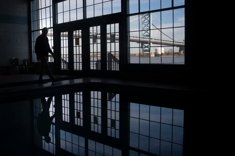 Homeowner Steven Peikin is silhouetted in the pool area of the Pier 3 Condominium building in Philadelphia.
