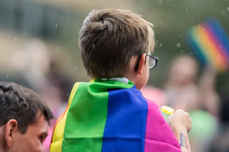 Toronto, Canada – July 3, 2016: A child wears a rainbow flag in support of LGBTQ rights.