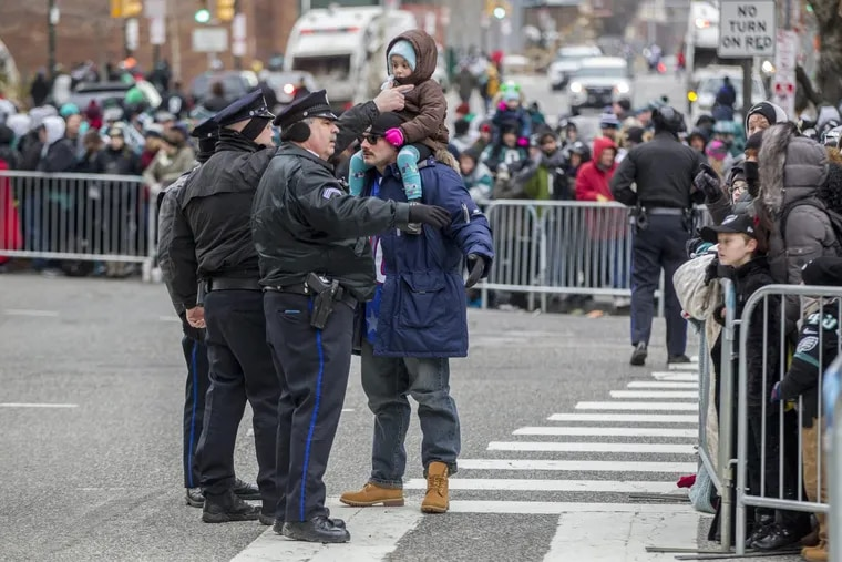 Philadelphia Police tell a spectator that he cannot be in the street at 16th and the Parkway early Thursday morning on the day of the Eagles Parade.