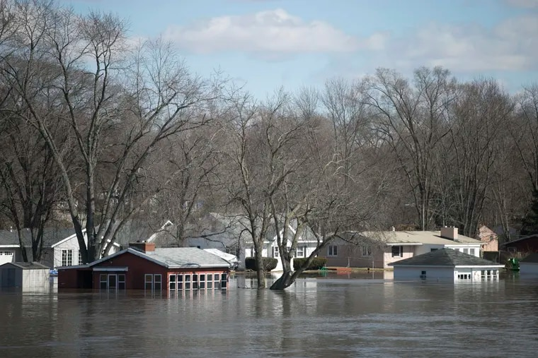 The Rock River crested its banks and floods Shore Drive, seen here on Saturday, March 16, 2019, from the Bauer Parkway bridge in Machesney Park, Ill. Many rivers and creeks in the Midwest are at record levels after days of snow and rain.