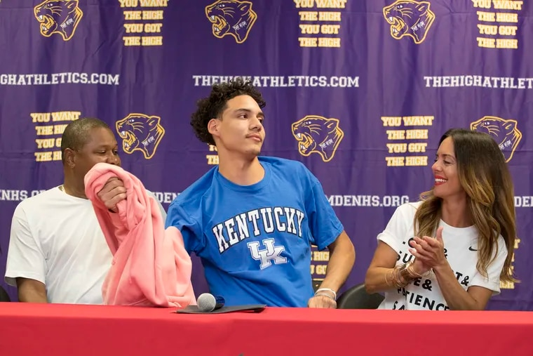 Flanked by his parents, Stephen Ware and Monique Ware, Camden High basketball star Lance Ware announced he will attend Kentucky by pulling off his sweatshirt to reveal his choice on a T-shirt.