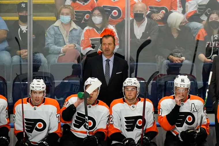 Philadelphia Flyers head coach Alain Vigneault stands behind his bench during the second period of a NHL preseason hockey game Tuesday, Oct. 5, 2021, in Bridgeport, Conn. (AP Photo/Frank Franklin II)