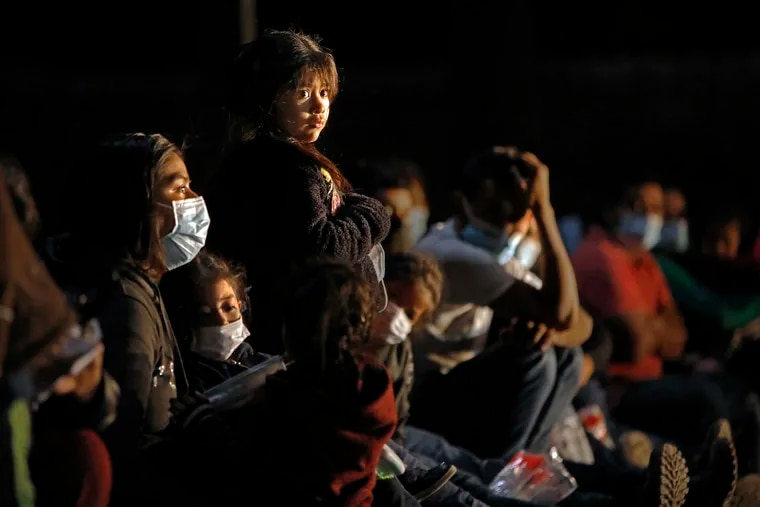 A young girl is held close by her mother as they wait with others to be processed by Border Patrol agents after crossing the Rio Grande in a raft on Thursday.