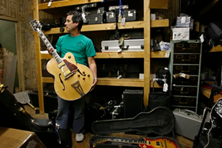 Business at his Society Hill Loan is up about 20 percent over last year, Nat Leonard says. He is holding one of many guitars there; among them, he says, are 30 pawned by a Grammy-winning musician hurt by the real estate slump.