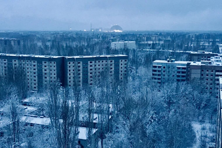 On the roof of a 16-story apartment building in Pripyat at sunset, a visitor can see what remains of the abandoned town. The only light comes from the Chernobyl nuclear station and the giant containment shield covering the remains of the exploded reactor.