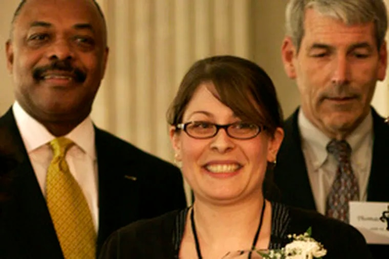Gina S. Hart, 29, holds her Dr. Ruth Wright Hayre Teacher of the Year Award. Behind her are union chief Jerry Jordan (left) and interim district chief Thomas Brady.