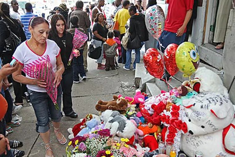 Elaine Torres (left) and Jennifer Diaz (behind her) add flowers to the growing memorial to the victims of the car crash on Third Street in Feltonville. (Michael Bryant/Staff Photographer)