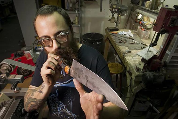 Custom knife maker Adam Balkovic of Biltsharp Manufacturing Co. checks the edge and his handmade knives in his workshop in Philadelphia. ( ALEJANDRO A. ALVAREZ / STAFF PHOTOGRAPHER )