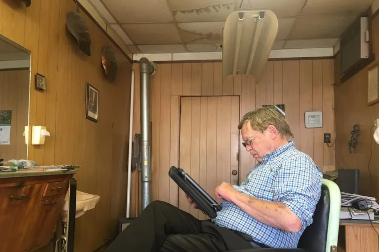 Lee Bendinsky uses a neighboring business's Wi-Fi to access his tablet in his barbershop in Wyalusing, Bradford County.
