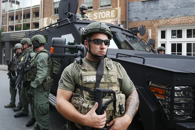 Members of a SWAT team keep an eye on demonstrators marking the one year anniversary of the Unite The Right rally in Charlottesville, Va., Sunday, Aug. 12, 2018.