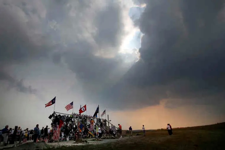 2006: The late-afternoon sun peeks through the clouds at a temporary memorial at the crash site on the day before the fifth anniversary.
