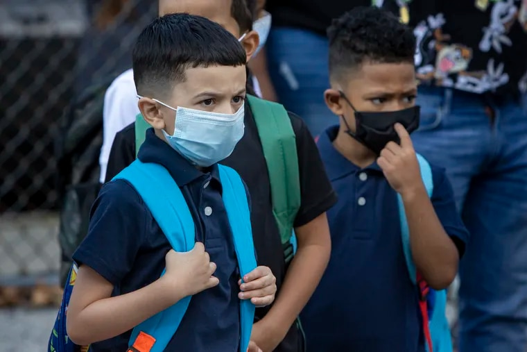Young kids in masks waiting for instructions from teacher before being escorted into their first grade class at the Davis Family School in Camden.