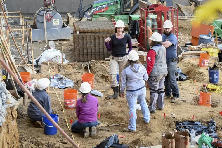 Volunteer archeologists work to exhume bodies buried at the former First Baptist burial ground in March. BRIANNA SPAUSE / Staff Photographer