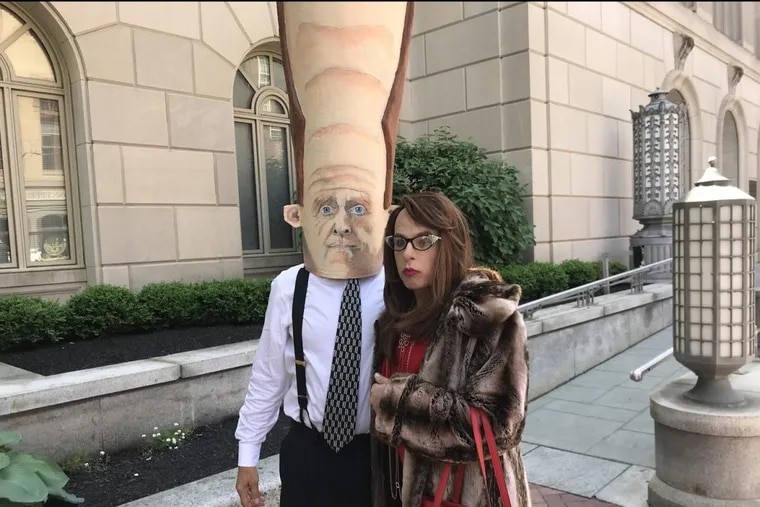 Mike Hisey, as billionaire hedge fund heiress Rebekah Mercer (r), encounters the big giant head of a mock Pat Toomey, worn by Lancaster's Neil Gussman.