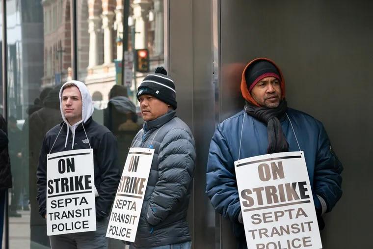 Transit officers (from left) Derek Vanderslice, Alex Svay, and Don Davis, picket outside SEPTA headquarters on Market Street in Philadelphia.
