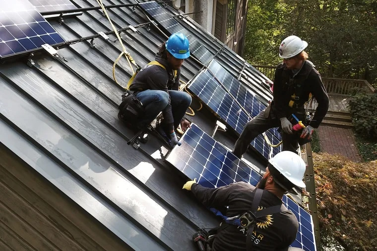 Installers from Solar States LLC attach solar panels to the roof Bill and Yolanda Hopping's house on Oct. 22.