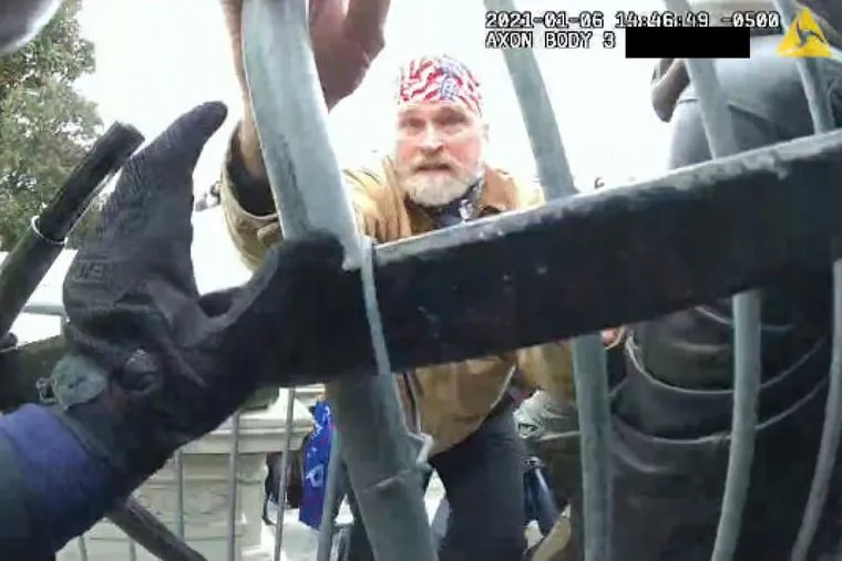 A man the FBI has identified as Philip S. Young, a retired boilermaker from Sewell, N.J., pushes against police barricades outside the Capitol in this still from a Metropolitan Police officer's bodycam.
