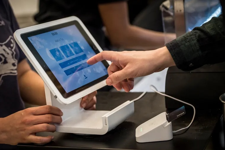 A customer uses a Square Inc. device to make a payment. Bloomberg photo by David Paul Morris