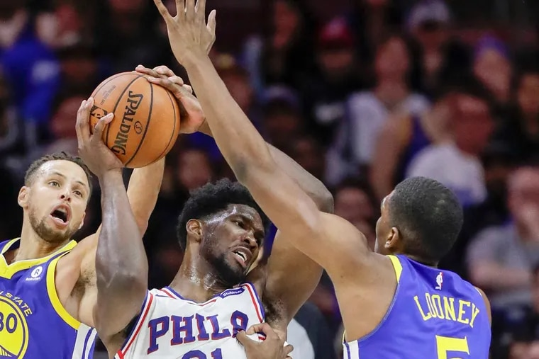 Sixers center Joel Embiid (center) and Warriors guard Stephen Curry (left) are both sidelined for Tuesday's game.