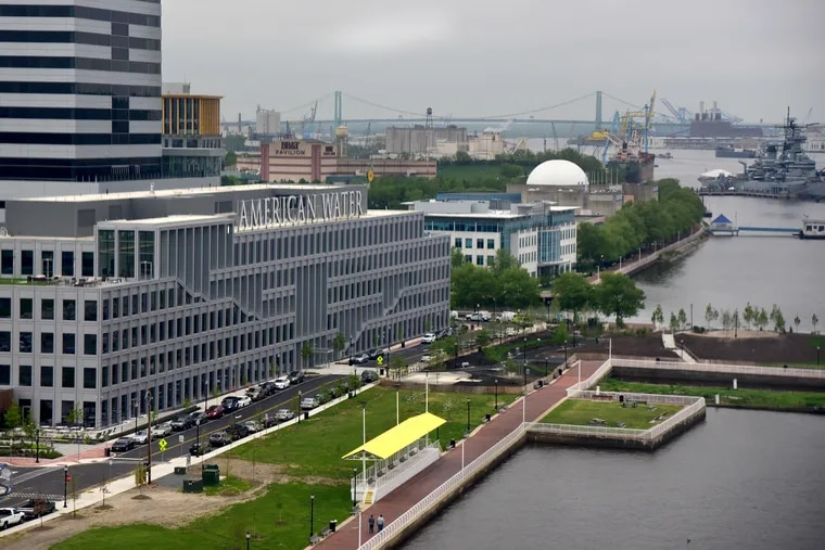 A May 2019 view of the Camden Waterfront shows, at the rear and from the left: One Port Center; the BB&T Pavilion; the Adventure Aquarium; and the Battleship New Jersey. In the center from left to right are the Triad 1828 tower; the corporate headquarters of American Water; and the Ferry Terminal Building.